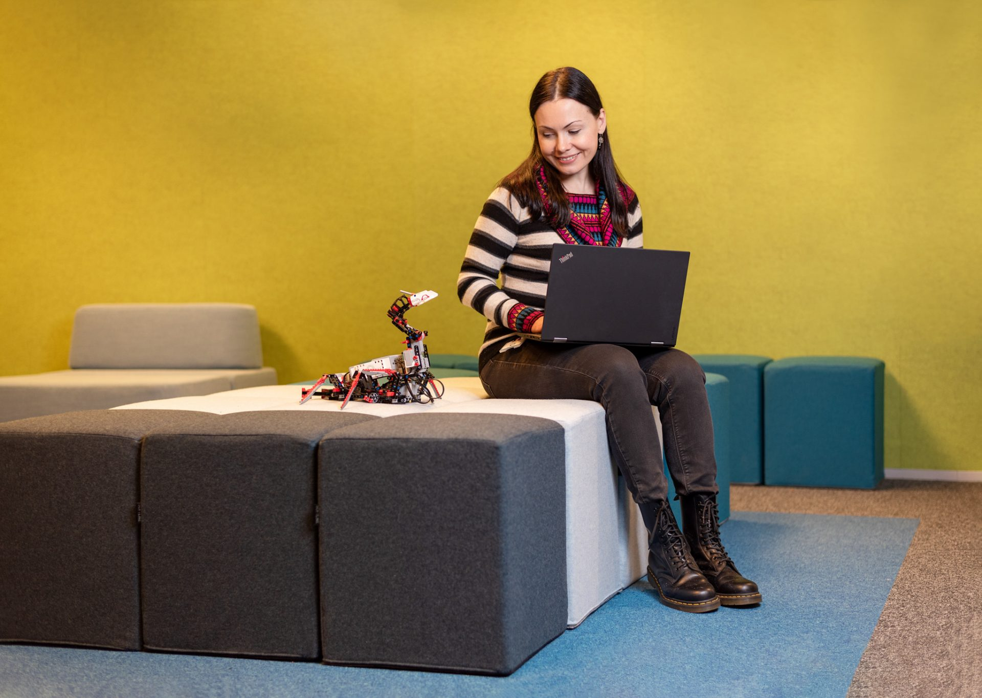 Test Engineer Karina Pietere sitting with her laptop and a toy robot.